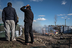 © London News Pictures. Calais, France. 04/03/16. Refugees watch on as a group of shelters are razed to the groun by a fire. French authorities are clearing the southern half of the Calais 'Jungle' camp, which charities estimate to contain 3,500 people. Photo credit: Rob Pinney/LNP