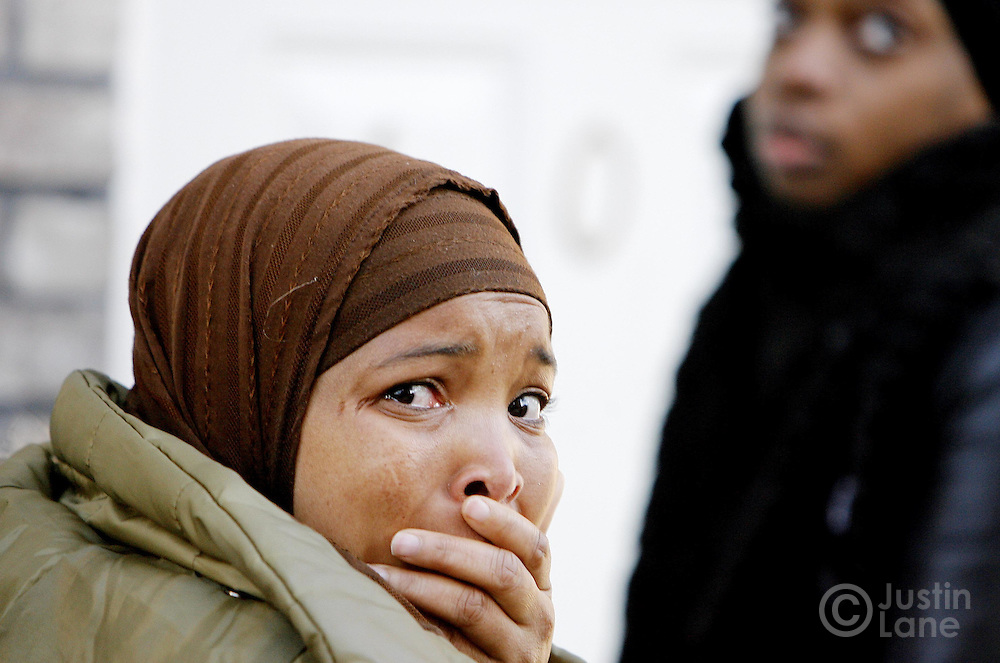 Two women stand outside of a house where 9 people were killed, 8 of them children, in an overnight fire in the Bronx, New York on Thursday 08 March 2007. The two entered a nearby house where members of the family were gathering.