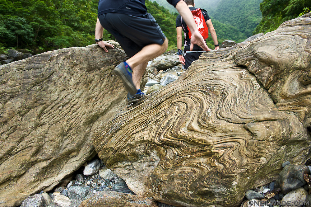 A river tracer climbs over a textured rock as he ascends a stream near Taroko Gorge, Taiwan.