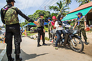 "25 OCTOBER 2012 - TAK BAI, NARATHIWAT, THAILAND: Thai women Rangers (paramilitary operating under Army command) pull over Muslim women at a checkpoint in Tak Bai, Thailand. The ""Tak Bai Incident"" took place on Oct. 25 in Tak Bai, Narathiwat, Thailand during the Muslim insurgency in southern Thailand. On that day, a crowd gathered to protest the arrest of local residents. Police made hundreds of arrests during the protest and transported the arrested to Pattani, about two hours away, in another province. They were transported in locked trucks and more than 80 people suffocated en route. This enraged local Muslims and shocked people across Thailand. No one in the Thai army accepted responsibility for the deaths and no one was ever charged. In the past, the anniversary of the incident was marked by protests and bombings. This year it was quiet. More than 5,000 people have been killed and over 9,000 hurt in more than 11,000 incidents, or about 3.5 a day, in Thailand's three southernmost provinces and four districts of Songkhla since the insurgent violence erupted in January 2004, according to Deep South Watch, an independent research organization that monitors violence in Thailand's deep south region that borders Malaysia.   PHOTO BY JACK KURTZ"
