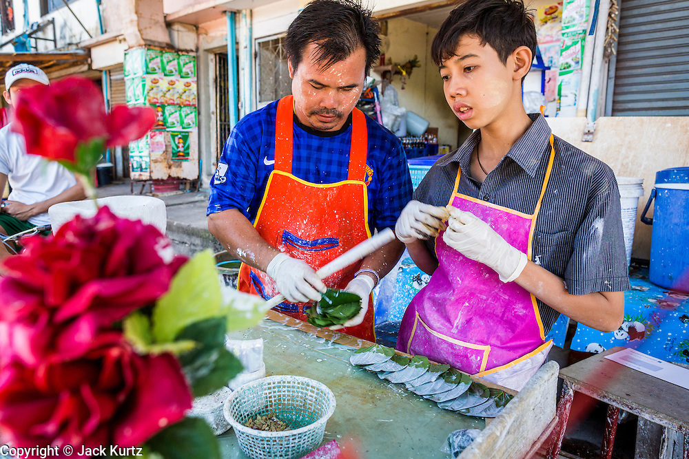 30 APRIL 2013 - MAHACHAI, SAMUT SAKHON, THAILAND: A Burmese betel nut vendor a his son prepare betel leafs for his Burmese customers who work in fish processing plants in the Thai fishing port of Mahachai. The Thai fishing industry is heavily reliant on Burmese and Cambodian migrants. Burmese migrants crew many of the fishing boats that sail out of Samut Sakhon and staff many of the fish processing plants in Samut Sakhon, about 45 miles south of Bangkok. Migrants pay as much $700 (US) each to be smuggled from the Burmese border to Samut Sakhon for jobs that pay less than $5.00 (US) per day. There have also been reports that some Burmese workers are abused and held in slavery like conditions in the Thai fishing industry.           PHOTO BY JACK KURTZ