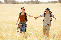 Hiking couple holding hands walking through field