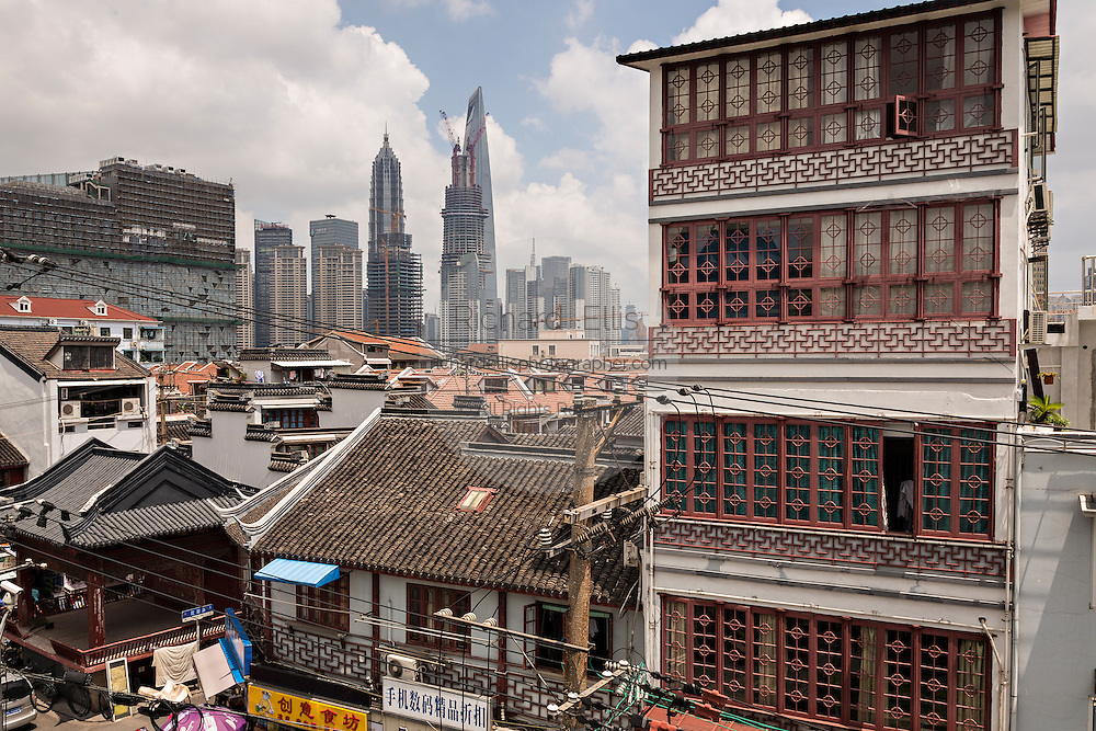 Traditional chinese tile roofs contrast the modern skyline of Shanghai, China