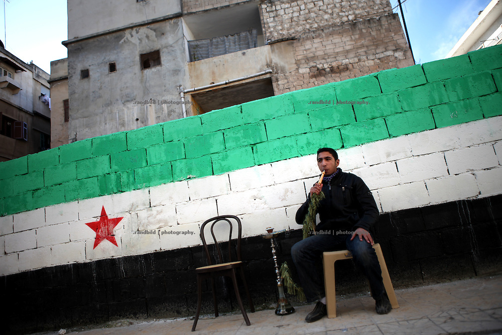 A young man smokes a water pipe on the sidewalk in front of a huge graffity showing the flag of the revolution in Idlib, Province of Idlib, Syria.