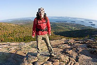 Young woman hiking on Cadillac Mountain in Acadia National Park. Bar Harbor, Maine.<br />