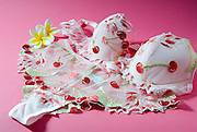 female underwear Bra and Panties with cherry design, on pink background