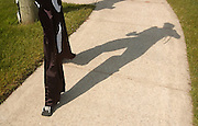 25 year old Neil Sauter casts a long late afternoon shadow as he walks toward downtown Charlevoix during his walk on stilts across Michigan to raise money and awarness for Cerebral Palsy.  Suater is walking from Toledo, Ohio to Ironwood, Michigan and hopes to raise $10,000.00.
