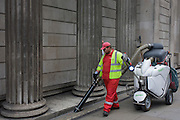 A corporation of London street cleaner with contactor Amey plc, hoovers litter beneath pillars of the Bank of England.