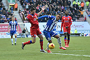 Wigan Athletic Defender, Reece Wabara and Oldham Athletic Defender, Danny Lafferty tussle for a ball in the middle of the pitch during the Sky Bet League 1 match between Wigan Athletic and Oldham Athletic at the DW Stadium, Wigan, England on 13 February 2016. Photo by Mark Pollitt.