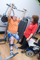 Disabled man using the chest press under instruction from a member of staff at his sport leisure centre,
