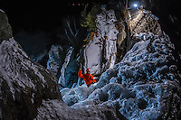 A top-view perspective on Jeff Mercier, professional alpine climber, swinging one ice tool during a rapid night ascent of Cascatte di Lillaz icefall.