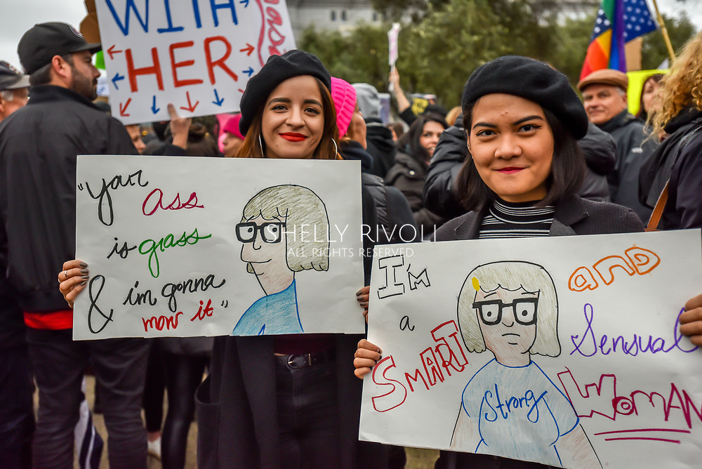 Two young women wear black berets and hold humorous cartoon signs at the Womens March rally at Civic Center Plaza.