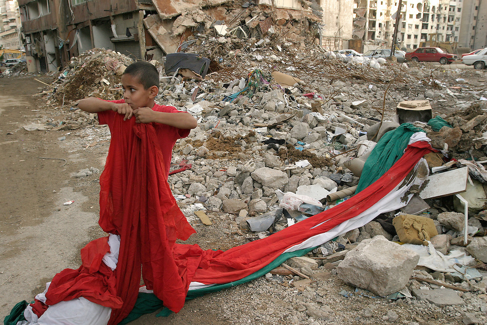 A boy tears fabric from a giant Lebanese flag in the ruins of an apartment building in the Hezbollah stronghold of Haret Hriek, South Beirut.