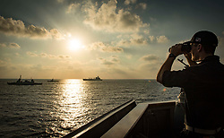 MEDITERRANEAN SEA (Aug. 7, 2018) Ensign Jordan Whittle observes the Israeli Navy Sa'ar 5-class corvette INS Lahav, left, the Sa'ar 4.5-class corvette INS Sufa, center, and the Military Sealift Command fast-combat support ship USNS Leroy Grumman (T-AOE 195) from aboard the Arleigh Burke-class guided-missile destroyer USS Carney (DDG 64) during exercise Reliant Mermaid 2018. Reliant Mermaid is a maritime search and rescue and anti-terrorism force protection exercise hosted by the Israel Defense Forces designed to increase interoperability by enhancing individual and collective maritime proficiencies of participating nations and promote interoperability, mutual understanding and cooperation. (U.S. Navy photo by Mass Communication Specialist 1st Class Ryan U. Kledzik/Released)180807-N-UY653-996