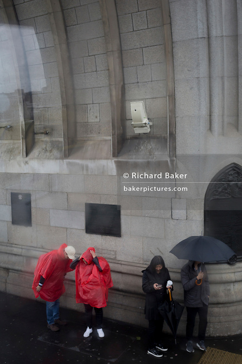 Tourists shelter from a wet and windy Tower Bridge, on Tower Bridge, on 8th May 2019, in London, England.