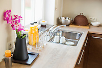 Flower vase with juice bottles on kitchen counter