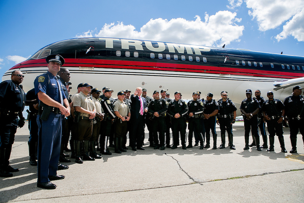 DETROIT, MI - SEPTEMBER 3, 2016: Republican presidential nominee Donald J. Trump poses for photos with law enforcement officials who helped escort his motorcade outside his plane on the tarmac at Detroit Metropolitan Wayne County Airport after attending a service at the Great Faith Ministries International church in Detroit, Michigan. CREDIT: Sam Hodgson for The New York Times.