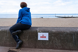Portobello, Scotland, UK. 9 May 2020. Images from holiday weekend Saturday afternoon during Covid-19 lockdown on promenade at Portobello. Promenade and beach were relatively quiet with a low key police presence. Pictured;  Woman sitting on sea wall next to sign saying No Sitting. Iain Masterton/Alamy Live News