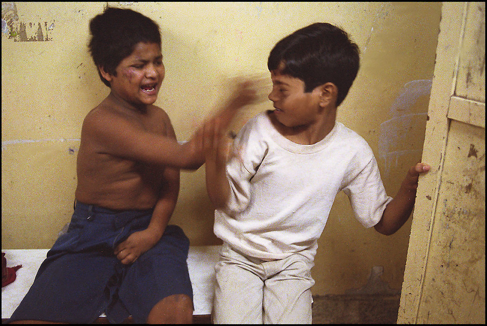 INDIA. Mumbai (Bombay). 2002. A mentally handicapped child (left) fights back while being bullied by a stronger boy. Being subjected to violence through bullying is very common for new comers to the shelter. The disabled child came to the shelter with injuries; neither the social workers nor the children at the shelter had any information about this person.