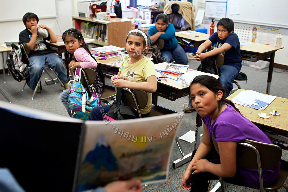 Pupils are reading a book containing handmade drawings about nature and preservation, and accompanied by verses in Goshute language, at the Ibapah Elementary School, in Ibapah, Deep Creek Valley, next to the Goshute Reservation, on the Nevada-Utah border, USA.