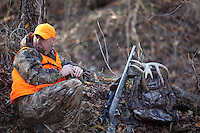 DEER HUNTER WEARING REALTREE AP CAMOUFLAGE AND BLAZE ORANGE GLASSES WITH BINOCULARS WHILE A THOMPSON CENTER OMEGA MUZZLELOADER LIES BESIDE HIM