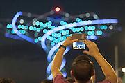 A visitor of Expo 2015 films with his smartphone the spectacle of the Tree of Life at the Lake Arena, Rho-Pero, Milan, in June 2015. The Tree of Life is the symbol of the Italian pavilion. &copy; Carlo Cerchioli<br /> <br /> Un visitatore di Expo 2015 riprende con il suo smartphone lo spettacolo dell'Albero della vita alla Lake Arena, Rho-Pero, Milano, giugno 2015. L'albero della vita &egrave; il simbolo del padiglione Italia.
