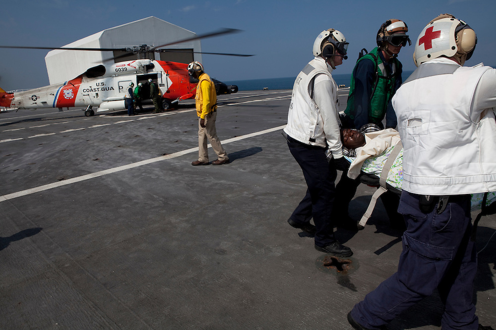 A Haitian earthquake victim with a broken leg is loaded off an U.S. Coast Guard helicopter after being air-lifted to the USNS Comfort, a naval hospital ship, for treatment on Wednesday, January 20, 2010 in Port-Au-Prince, Haiti. The Comfort deployed from Baltimore, bringing nearly a thousand medical personnel to care for victims of Haiti's recent earthquake.