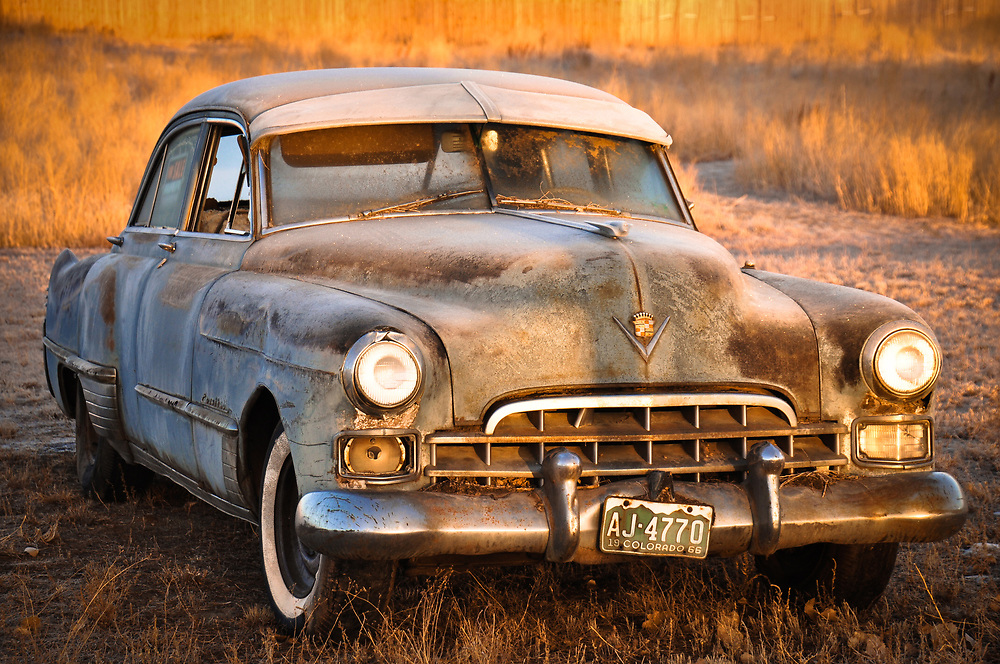 A picture of an old Cadillac out in the field.<br />