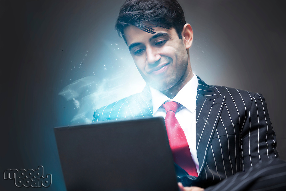 Young Indian Business Man using illuminated tablet