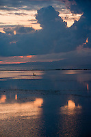 Fisherman with colossal clouds just before dawn off Sanur Beach in Bali, Indonesia.