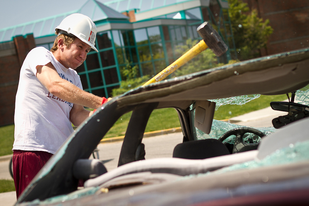 Andrew Platt '13 strikes the roof of the junked car during the car smashing study break outside the Harris Center. BEN BREWER/Grinnell College