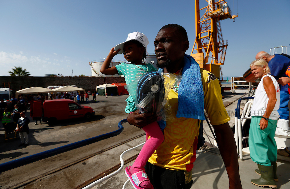 A sub-Saharan migrant carries his child while disembarking from the Migrant Offshore Aid Station (MOAS) ship MV Phoenix in Vibo Valentia, Italy, July 31, 2015.  195 migrants who were rescued off Libya on Wednesday arrived in Italy on Friday afternoon. The Phoenix, manned by personnel from international non-governmental organisations Medecins san Frontiere (MSF) and MOAS, is the first privately funded vessel to operate in the Mediterranean.<br /> REUTERS/Darrin Zammit Lupi <br /> MALTA OUT. NO COMMERCIAL OR EDITORIAL SALES IN MALTA