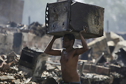 December 12, 2016 - Recife, Brazil - A man is seen carrying what is left of a stove. During the morning of Monday (12), the fire hit the favela Vila Santa Luzia, in the city of Recife. Dozens of people had their homes burned by fire and three men had severe burns on their bodies. In Recife, Northeast Brazil, December 12, 2016. (Credit Image: © Diego Herculano/NurPhoto via ZUMA Press)