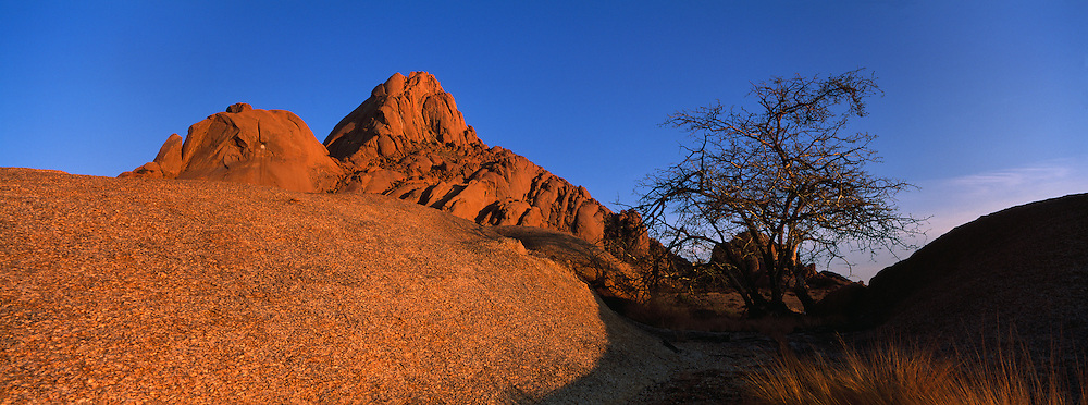 Africa, Namibia, Usakos, Morning sun lights granite rock formations surrounding Spitzkoppe mountain in Namib Desert