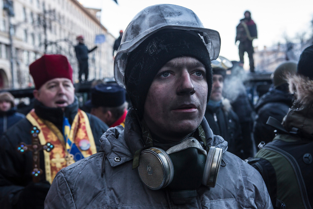KIEV, UKRAINE - JANUARY 24: An anti-government protester, his face blackened by the smoke of burning tires, pauses as the crowd sings the Ukrainian national anthem on January 24, 2014 in Kiev, Ukraine. After two months of primarily peaceful anti-government protests in the city center, new laws meant to end the protest movement have sparked violent clashes in recent days. (Photo by Brendan Hoffman/Getty Images) *** Local Caption ***