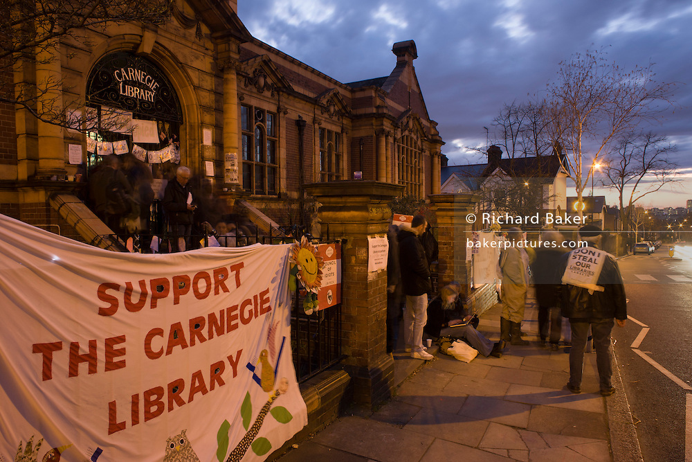 An evening meeting by campaigners outside Carnegie Library in Herne Hill, south London while occupiers remain inside the premises on day 6 of its occupation, 5th April 2016. The angry local community in the south London borough have occupied their important resource for learning and social hub for the weekend. After a long campaign by locals, Lambeth have gone ahead and closed the library's doors for the last time because they say, cuts to their budget mean millions must be saved.