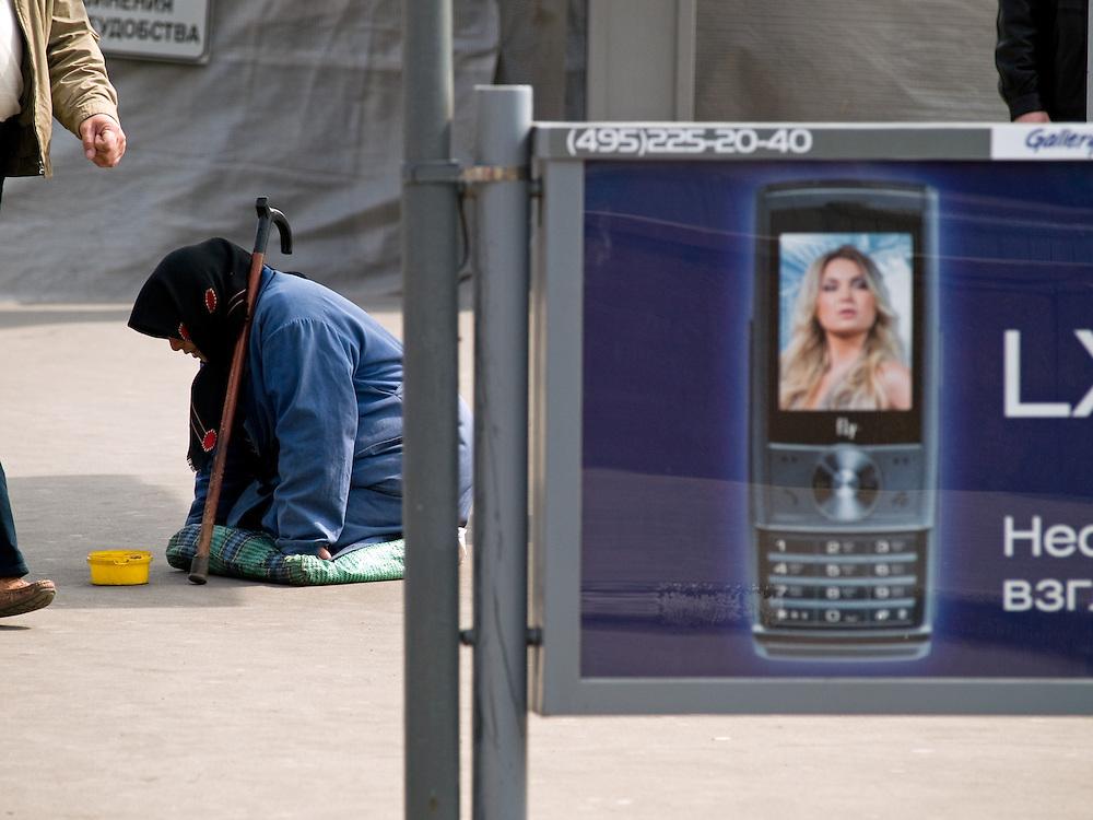 &Auml;ltere Frau bettelt vor einer Werbung f&uuml;r Mobiltelefone auf einer Stra&szlig;e im Zentrum der russischen Hauptstadt Moskau. <br /> <br /> Old woman is begging infront of an advertising for mobil phones on a street in the center of the Russian capitol Moscow.