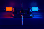 A colorful water droplet falls from a bathroom faucet with glowing handles.Black light