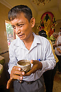 14 MARCH 2006 - PHNOM PENH, CAMBODIA: A man with a cup of holy water at a Buddhist shrine in central Phnom Penh, Cambodia. The water will be used to bathe a Buddhist icon or sprinkle on himself when he is done praying.  PHOTO BY JACK KURTZ