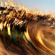 Waves break, reflecting golden light from a sunset.