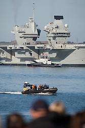 © Licensed to London News Pictures. 30/10/2017. Portsmouth, UK.  A police boat on patrol as the Royal Navy's flagship, HMS Queen Elizabeth, departs Her Majesty's Naval Base (HMNB) Portsmouth for the first time since her arrival on 16/08/2017.  The new aircraft carrier is heading back to sea for the second stages of her sea trials.<br /> <br /> Flight trials involving the new F-35B Joint Strike Fighter are expected to take place off the coast of the U.S. next year, and she is due to come into service in the early 2020s.  Photo credit: Rob Arnold/LNP