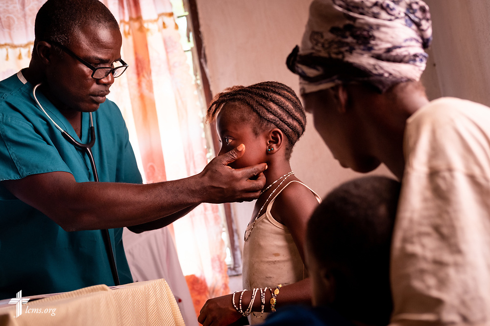 Michael N'Danema, a Sierra Leonean medical professional, examines a young patient on the fourth day of the LCMS Mercy Medical Team on Thursday, May 10, 2018, in the Yardu village outside Koidu, Sierra Leone, West Africa. LCMS Communications/Erik M. Lunsford