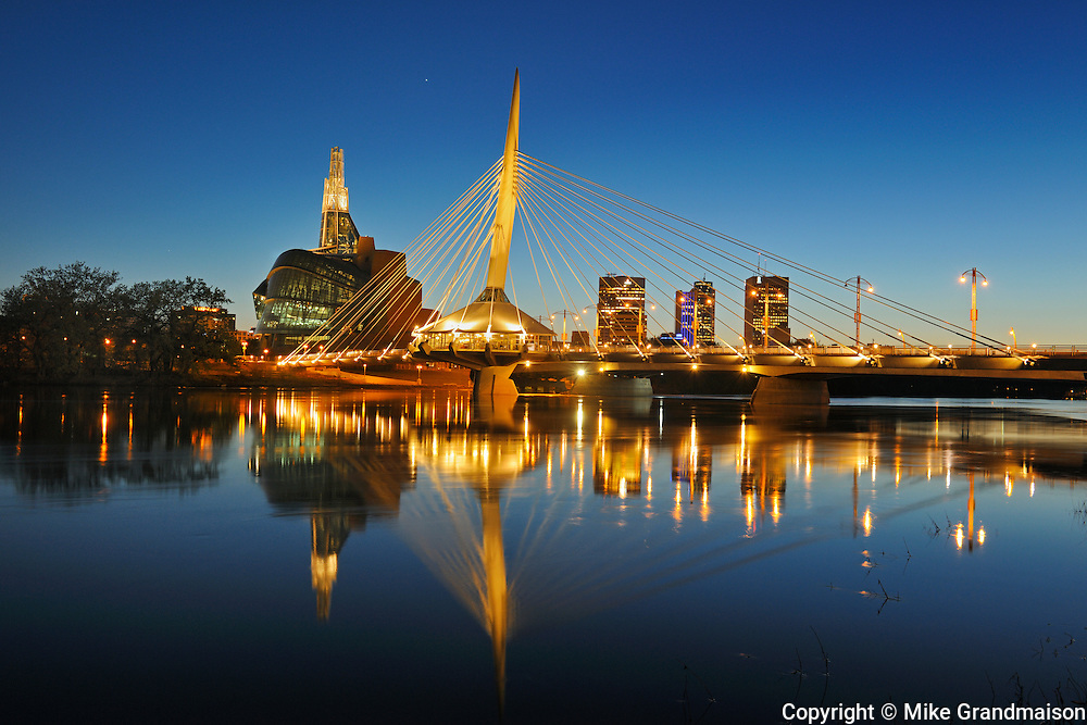 Red River and Winnipeg skyline with Canadian Museum for Human Rights and Esplanade Riel bridge at dusk<br /> Winnipeg<br /> Manitoba<br /> Canada