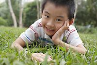 Boy (7-9) lying on grass in park portrait