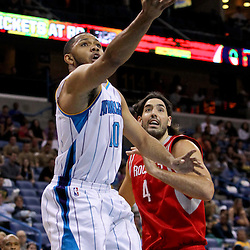 April 19, 2012; New Orleans, LA, USA; New Orleans Hornets shooting guard Eric Gordon (10) shoots over Houston Rockets power forward Luis Scola (4) during the first quarter at the New Orleans Arena. The Hornets defeated the Rockets 105-99.  Mandatory Credit: Derick E. Hingle-US PRESSWIRE