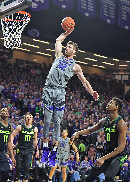 Dean Wade #32 of the Kansas State Wildcats drives past Flo Thamba #0 of the Baylor Bears for a slam dunk during the second half at Bramlage Coliseum in Manhattan, Kansas.