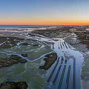 Aerial dusk seascape of oyster production, in Ria Formosa wetlands nature conservation park, Algarve. Portugal.