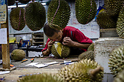 Teoh Nai Aun opens a durian at his roadside stall during the Durian Festival in Georgetown, Pulau Pinang, Malaysia on June 16th, 2019. The tropical fruit has become one of China's latest culinary fixations, sending the export demand and prices soaring, and becoming a point of attraction for tourists who come to Malaysia to try its famed varieties.  Photo by Suzanne Lee/PANOS for Los Angeles Times