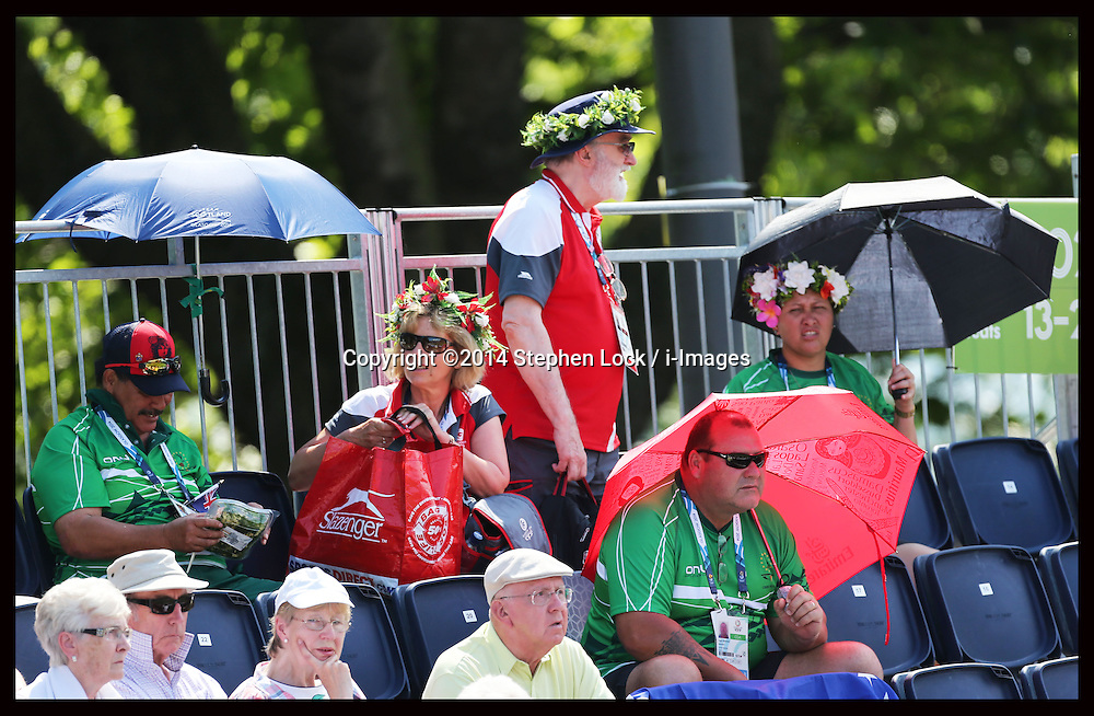 Image licensed to i-Images Picture Agency. 25/07/2014. Glasgow, United Kingdom. Umbrellas were the order of the day for spectators out in the hot weather as they watch the  Lawn Bowls competition  at the Kelvingrove Bowls Centre during day two of Commonwealth Games in Glasgow.  Picture by Stephen Lock / i-Images