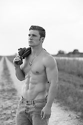 muscular shirtless man on a dirt road in the middle of nowhere
